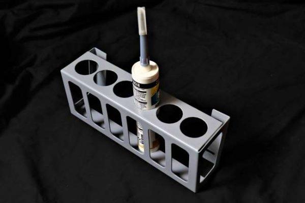 Deze metalen houder met een grijze poedercoatingbevat 6 gaten van Ø 50 mm waar elk een kitkoker in past.